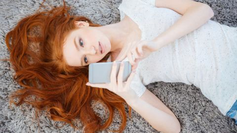 Redhead charming woman lying on the carpet and using smartphone at home