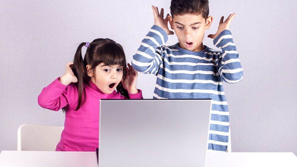 Little kids react with shock and awe while using a laptop. Internet safety for kids concept. Toned image with selective focus