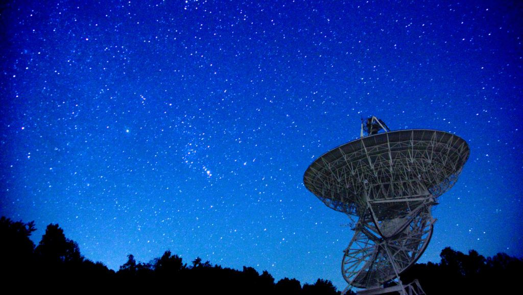 An older communications satellite sits abandoned, but in good condition looking into the starry night sky.