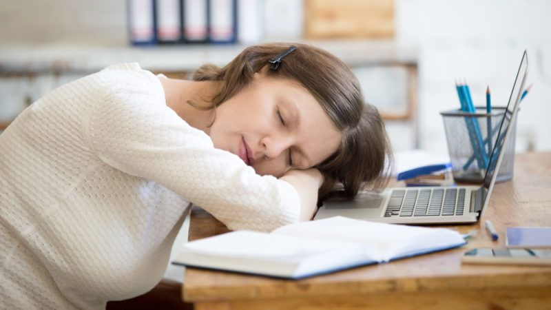 Portrait of young woman lying on the table in front of laptop, sleepy, tired, overworked or lazy to work. Attractive business woman napping in home office relaxing after work on laptop computer