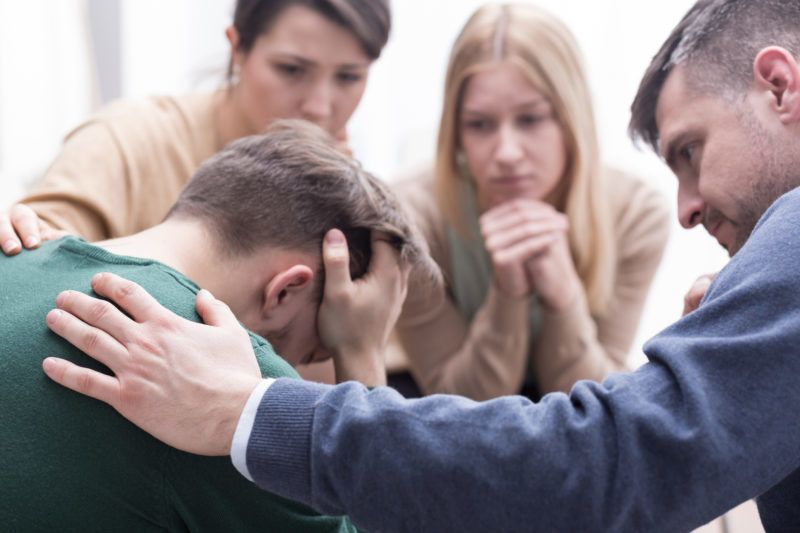 Close-up of a devastated young man holding his head in his hands and a group of friends in a supportive pose around him