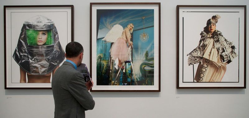 A visitor looks at photographs by British photographer David Bailey of (L to R) Abby Lee Kershaw, Cicciolina (Ilona Staller) and Anna Piaggi at an exhibition of his works where over 300 prints are exhibited in London on February 5, 2014. As well as new work, this exhibition includes a wide variety of Bailey's photographs from a career that has spanned more than half a century. AFP PHOTO/ANDREW COWIE RESTRICTED TO EDITORIAL USE, MANDATORY MENTION OF THE ARTIST UPON PUBLICATION, TO ILLUSTRATE THE EVENT AS SPECIFIED IN THE CAPTION / AFP PHOTO / ANDREW COWIE