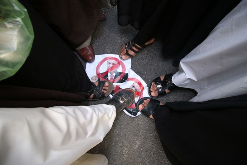 Iraqi tribesmen step on posters bearing a portrait of Turkish President Recep Tayyip Erdogan crossed out during a protest against the continued presence of Turkish troops in northern Iraq on October 16, 2016 outside the governorate building in the southern city of Basra.