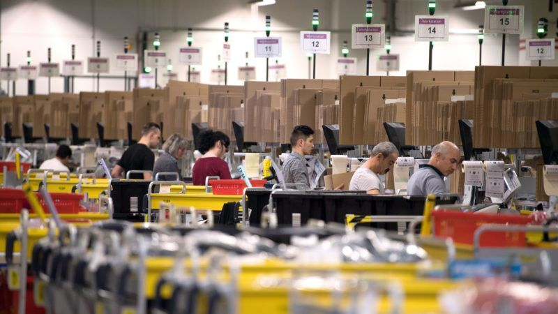 Employees of American electronic commerce company Amazon prepare products for dispatch in Bad Hersfeld, central Germany on December 7, 2017. To cope with the high-turnover Christmas business, Amazon has hired 13,000 temporary employees. / AFP PHOTO / dpa / Swen Pförtner / Germany OUT