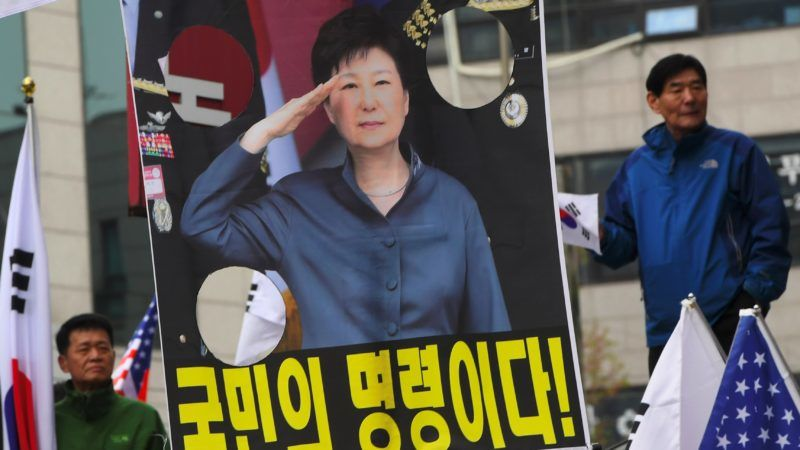 Supporters of South Korea's former president Park Geun-hye stand next to a picture of Park Geun-hye during a rally demanding her release outside the Seoul Central District Court in Seoul on April 6, 2018. A South Korean court was set to hand down its verdict on April 6, in the trial of disgraced former President Park Geun-hye, who faces up to 30 years in prison if convicted on multiple charges of bribery and abuse of power. / AFP PHOTO / Jung Yeon-je