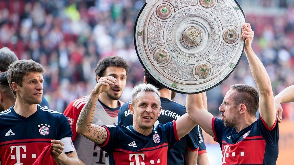 (L-R) Bayern Munich's German forward Thomas Mueller, Bayern Munich's Brazilian defender Rafinha and  Bayern Munich's French midfielder Franck Ribery celebrate with a mock-up of the Bundesliga trophy after the German first division Bundesliga football match 1 FC Augsburg vs FC Bayern Munich  in Augsburg, southern Germany, on April 7, 2018. / AFP PHOTO / dpa / Andreas Gebert / Germany OUT / RESTRICTIONS: DURING MATCH TIME: DFL RULES TO LIMIT THE ONLINE USAGE TO 15 PICTURES PER MATCH AND FORBID IMAGE SEQUENCES TO SIMULATE VIDEO. == RESTRICTED TO EDITORIAL USE == FOR FURTHER QUERIES PLEASE CONTACT DFL DIRECTLY AT + 49 69 650050