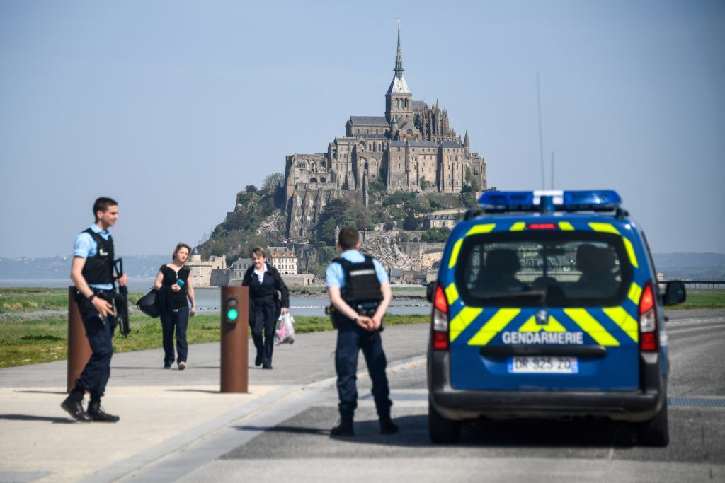 "People stand on the road leading to the Mont-Saint-Michel as Gendarmes block the access after it was evacuated on April 22, 2018 of its tourists and residents ""as a precautious measure"" after an unidentified suspect allegedly threatened to attack law enforcement members. / AFP PHOTO / Damien MEYER"