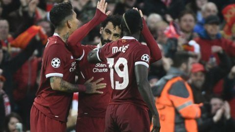 Liverpool's Egyptian midfielder Mohamed Salah (C) celebrates after scoring with Liverpool's Brazilian midfielder Roberto Firmino (L) and Liverpool's Senegalese midfielder Sadio Mane during the UEFA Champions League first leg semi-final football match between Liverpool and Roma at Anfield stadium in Liverpool, north west England on April 24, 2018. / AFP PHOTO / Filippo MONTEFORTE