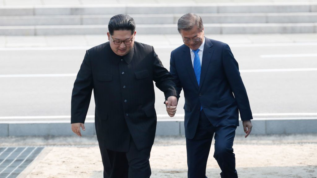 North Korea's leader Kim Jong Un (L) steps with South Korea's President Moon Jae-in (R) across the Military Demarcation Line that divides their countries ahead of their meeting at the official summit Peace House building at Panmunjom on April 27, 2018. The two men briefly stepped back over the line into the North before walking to the Peace House building on the southern side of the truce village of Panmunjom for the summit -- only the third of its kind since hostilities ceased in 1953. / AFP PHOTO / Korea Summit Press Pool / Korea Summit Press Pool