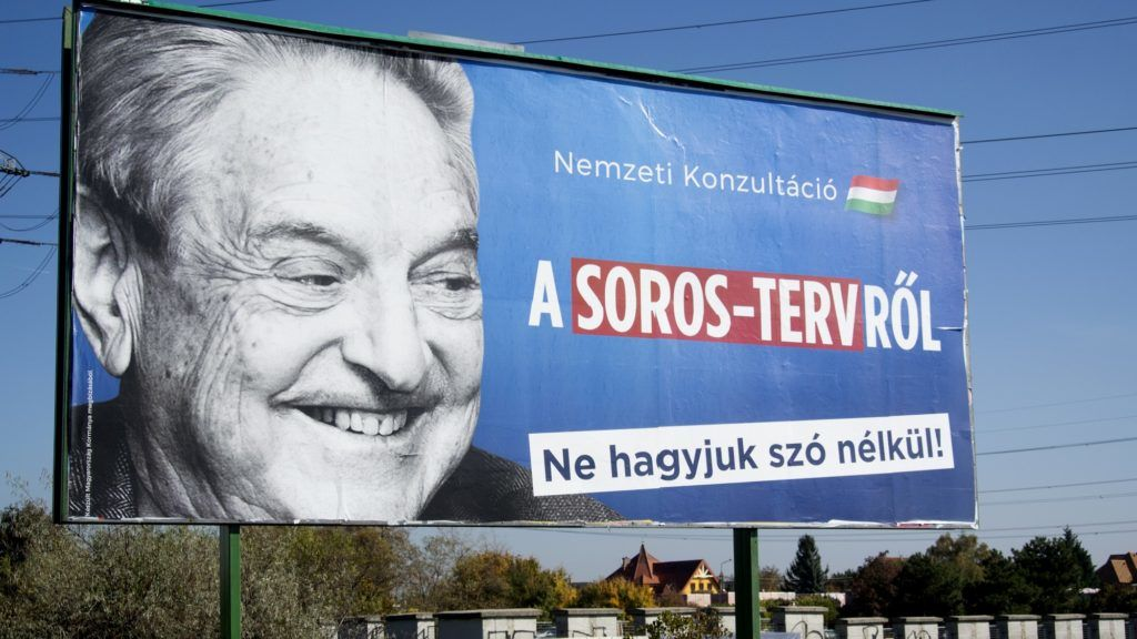 """A billboard with a poster of Hungarian-American billionaire and philanthropist George Soros with the lettering """"National consultation about the Soros' plan - Don't let it pass without any words"""" is seen in the 22nd district of Budapest on October 16, 2017, as the conservative government prepares their new national consultation. Since 2013, once one of Europe's most far-right parties Jobbik, whose members burned EU flags and called Jewish lawmakers a national security risk, has been lurching toward the political centre. And as Hungary readies for an election on April 8 Jobbik, which polls show is the strongest party behind Prime Minister Viktor Orban's ruling Fidesz, claims it is ready for government. An expert on the Hungarian far-right Peter Kreko says Orban's sharpening edge has forced Jobbik, who have criticised his relentless attacks on Soros and civil society groups, toward the centre. / AFP PHOTO / ATTILA KISBENEDEK"""