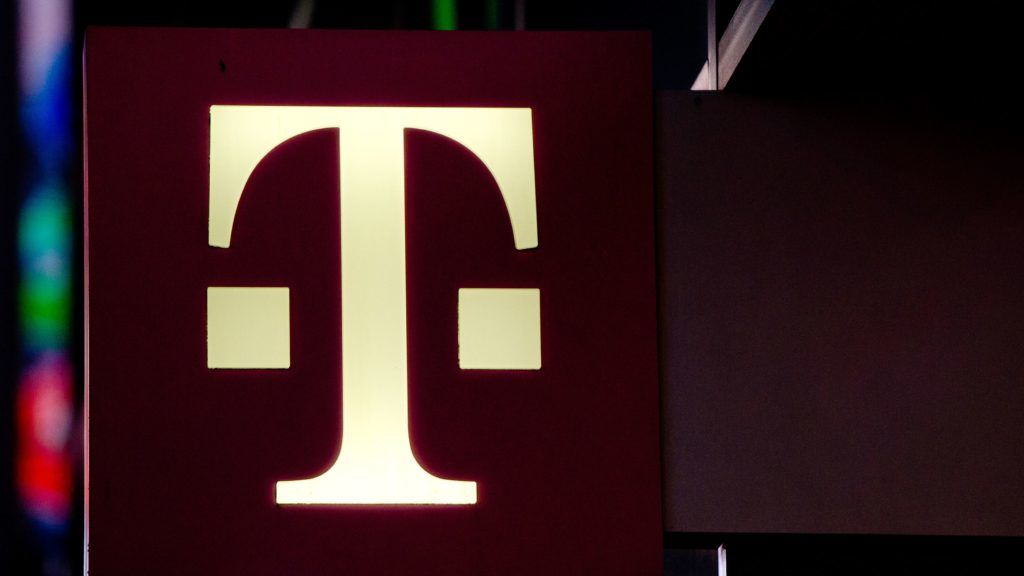The logo of the cellular phone company T-Mobile illuminated in New York City, 27 September, 2014. Photo: Daniel Bockwoldt/dpa