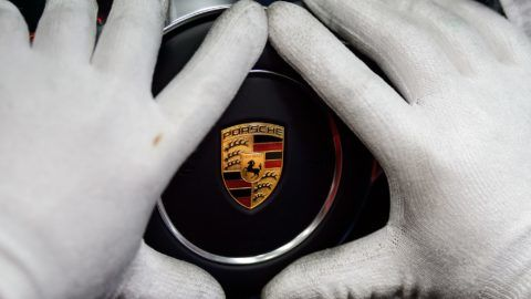 An employee attaches the logo of German automobile company Porsche to a car its manufacturing facilities in Stuttgart,Germany, 26 January 2018. Photo: Sina Schuldt/dpa