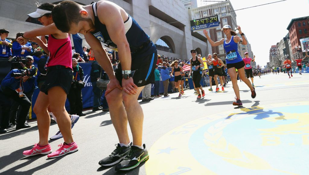BOSTON, MA - APRIL 18: Runners react after crossing the finish line to complete the 120th Boston Marathon on April 18, 2016 in Boston, Massachusetts.   Maddie Meyer/Getty Images/AFP
