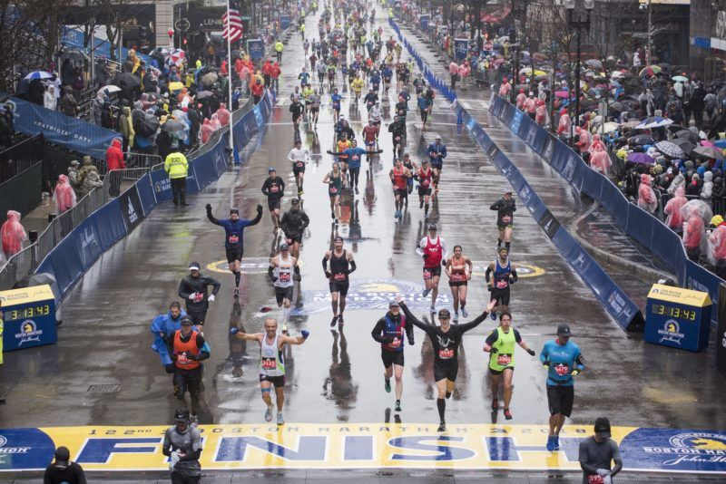 Runners come to the finish line of the 122nd Boston Marathon, where rain and high winds battered down for the duration. Monday April 16, 2018.  / AFP PHOTO / RYAN MCBRIDE