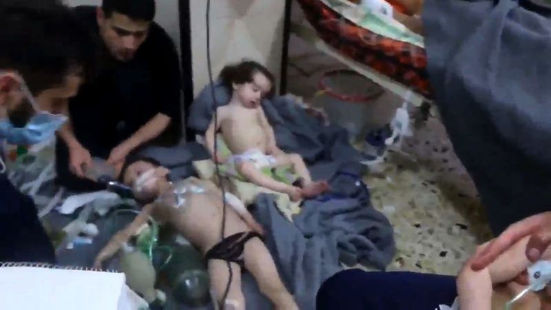 """An image grab taken from a video released by the Syrian civil defence in Douma shows unidentified volunteers giving aid to children at a hospital following a reported chemical attack on the rebel-held town on April 8, 2018. A suspected chemical attack by Syria's regime sparked international outrage, after rescue workers reported dozens killed by poison gas on rebel-held parts of Eastern Ghouta near Damascus. President Bashar al-Assad's regime and its ally Russia denied the allegations of a chlorine gas attack on the town of Douma, calling them """"fabrications"""".   / AFP PHOTO / AFP PHOTO AND SYRIA CIVIL DEFENCE / HO / === RESTRICTED TO EDITORIAL USE - MANDATORY CREDIT """"AFP PHOTO / HO / SYRIA CIVIL DEFENCE"""" - NO MARKETING NO ADVERTISING CAMPAIGNS - DISTRIBUTED AS A SERVICE TO CLIENTS ==="""