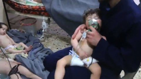 """An image grab taken from a video released by the Syrian civil defence in Douma shows an unidentified volunteer holding an oxygen mask over a child's face at a hospital following a reported chemical attack on the rebel-held town on April 8, 2018. A suspected chemical attack by Syria's regime sparked international outrage, after rescue workers reported dozens killed by poison gas on rebel-held parts of Eastern Ghouta near Damascus. President Bashar al-Assad's regime and its ally Russia denied the allegations of a chlorine gas attack on the town of Douma, calling them """"fabrications"""".   / AFP PHOTO / AFP PHOTO AND SYRIA CIVIL DEFENCE / HO / === RESTRICTED TO EDITORIAL USE - MANDATORY CREDIT """"AFP PHOTO / HO / SYRIA CIVIL DEFENCE"""" - NO MARKETING NO ADVERTISING CAMPAIGNS - DISTRIBUTED AS A SERVICE TO CLIENTS ==="""