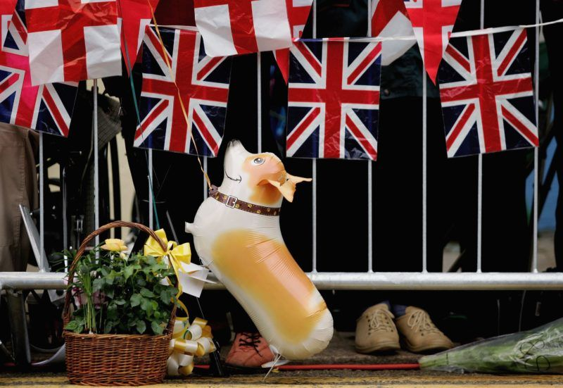 WINDSOR, UNITED KINGDOM - APRIL 21: A balloon of a Corgi dog is seen as people gather near Windsor Castle on April 21, 2006 in Windsor, England. HRH Queen Elizabeth II will take part in her traditional walk in the town later today to celebrate her 80th Birthday. In the evening the Prince of Wales will host a private party for The Queen and other members of the Royal family at Kew Palace.  (Photo by Daniel Berehulak/Getty Images)