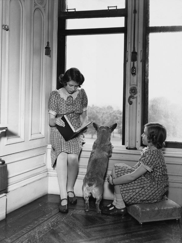 Princess Elizabeth reads to her sister Princess Margaret and Jane the corgi by a window in Windsor Castle. Princess Elizabeth is the future Queen Elizabeth II of England. (Photo by © Hulton-Deutsch Collection/CORBIS/Corbis via Getty Images)