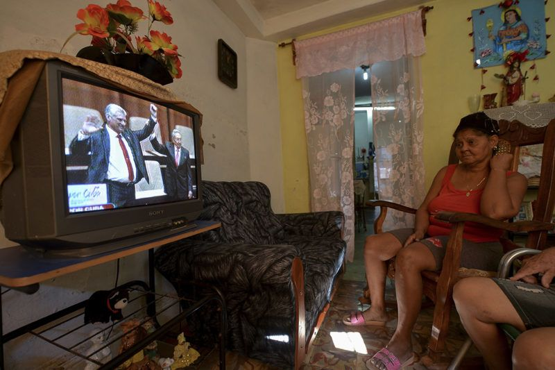 A woman watches on TV at her house in Havana as outgoing Cuban President Raul Castro (R) raises the arm of Cuba's new President Miguel Diaz-Canel after he was formally named by the National Assembly on April 19, 2018. Miguel Diaz-Canel succeeds Raul Castro -- a historic handover ending six decades of rule by the Castro brothers. The 57-year-old Diaz-Canel, who was the only candidate for the presidency, was elected to a five-year term with 603 out of 604 possible votes in the National Assembly.  / AFP PHOTO / Yamil LAGE