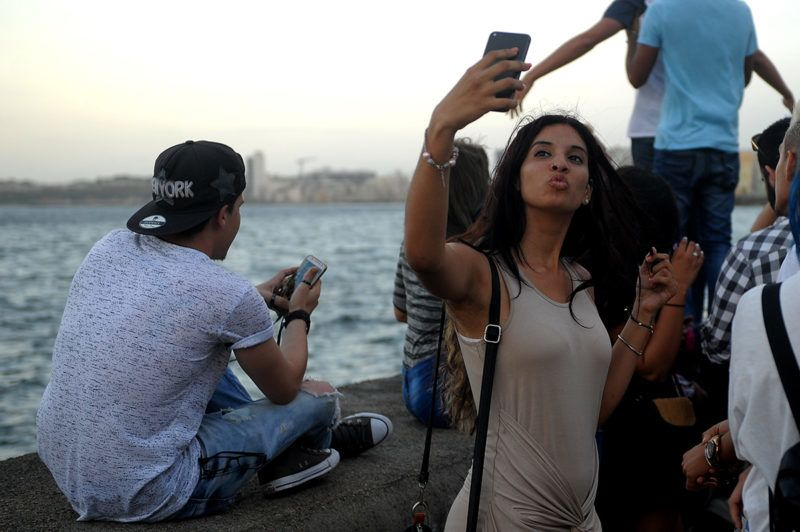 A young Cuban woman takes a selfie in Havana's Malecon, on April 01, 2018.Cubans in their twenties, raised within the revolution, face times of change being aware of the role they will play in the future of the country. / AFP PHOTO / Yamil LAGE
