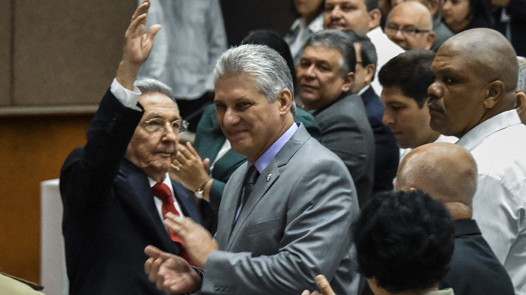 Cuban President Raul Castro (L) waves next to First Vice-President Miguel Diaz-Canel (C) during a National Assembly session that will select Cuba's Council of State ahead of the naming of a new president, in Havana on April 18, 2018.Cuban President Raul Castro steps down Thursday, passing the baton to a new generation in a transition that brings to a close the Castro brothers' six-decade grip on power. The 86-year-old has been in power since 2006, when he took over after illness sidelined his brother Fidel, who seized power in the 1959 revolution. / AFP PHOTO / STR