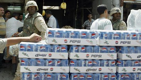 """""""LA GUERRE FINIE, LA BATAILLE DES BOISSONS GAZEUSES FAIT RAGE A BAGDAD"""" - Un soldat américain passe derrière un jeune vendeur de boissons gazeuses de la marque Pepsi, le 20 juin 2003 à Bagdad. AFP PHOTO/Marwan NAAMANI  US soldier walks behind an Iraqi boy selling the US soft drink Pepsi along a street in Baghdad 20 June 2003. The Pepsi sold in Iraq is manufactured in Iraq under license. With Saddam Hussein's regime gone, an influx of foreign-made cola brands has poured into Baghdad, setting off a cut-throat soft drinks war against the dominant Iraqi Pepsi Cola. AFP PHOTO/Marwan NAAMANI / AFP PHOTO / MARWAN NAAMANI"""