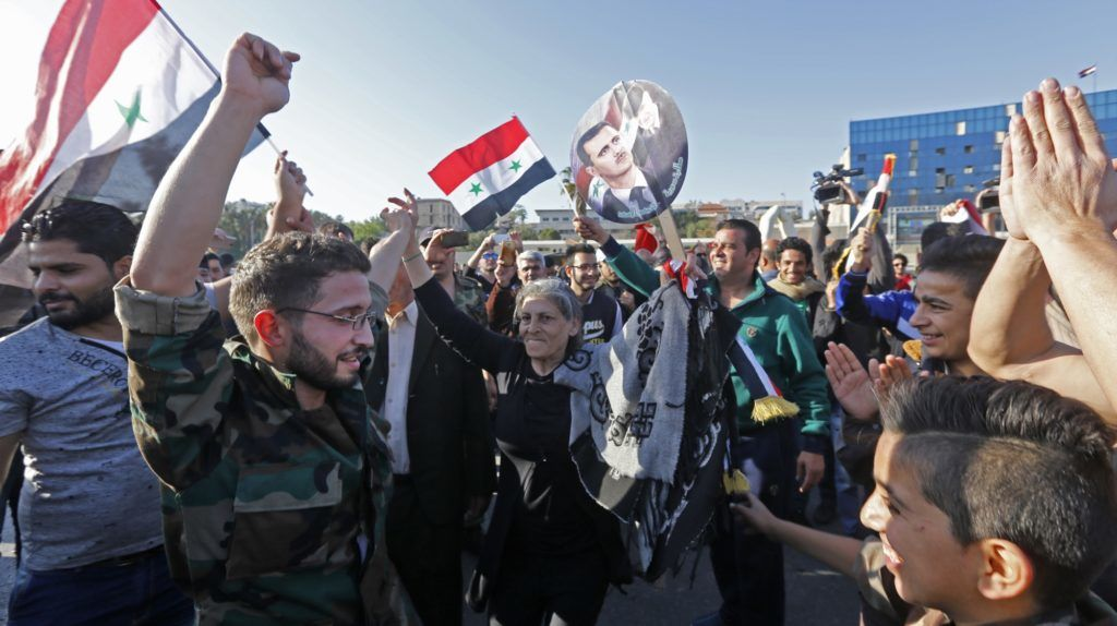 "Syrians wave the national flag and wave portraits of President Bashar al-Assad as they gather at the Umayyad Square in Damascus on April 14, 2018, to condemn the strikes carried out by the United States, Britain and France against the Syrian regime. The United States, Britain and France carried out a wave of punitive strikes against Bashar al-Assad's Syrian regime on Saturday in response to alleged chemical weapons attacks that President Donald Trump branded the ""crimes of a monster.""  / AFP PHOTO / LOUAI BESHARA"