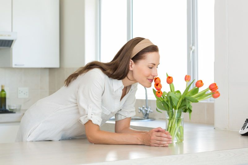 Smiling young woman smelling flowers in the kitchen at home