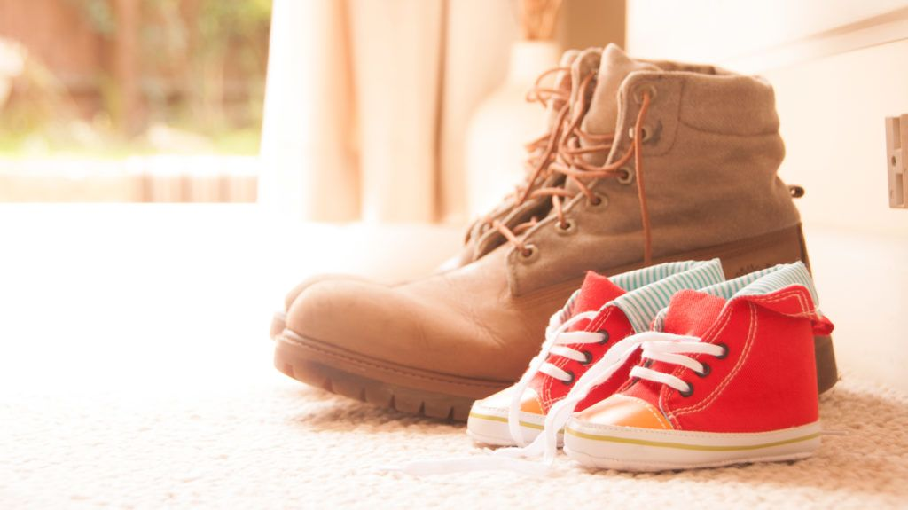 Shoes lined up at home with fathers large boots next to baby sons.