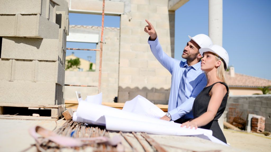 cute young woman architect with handsome foreman in building industry construction site