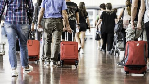 Travelers with suitcases walking through the airport