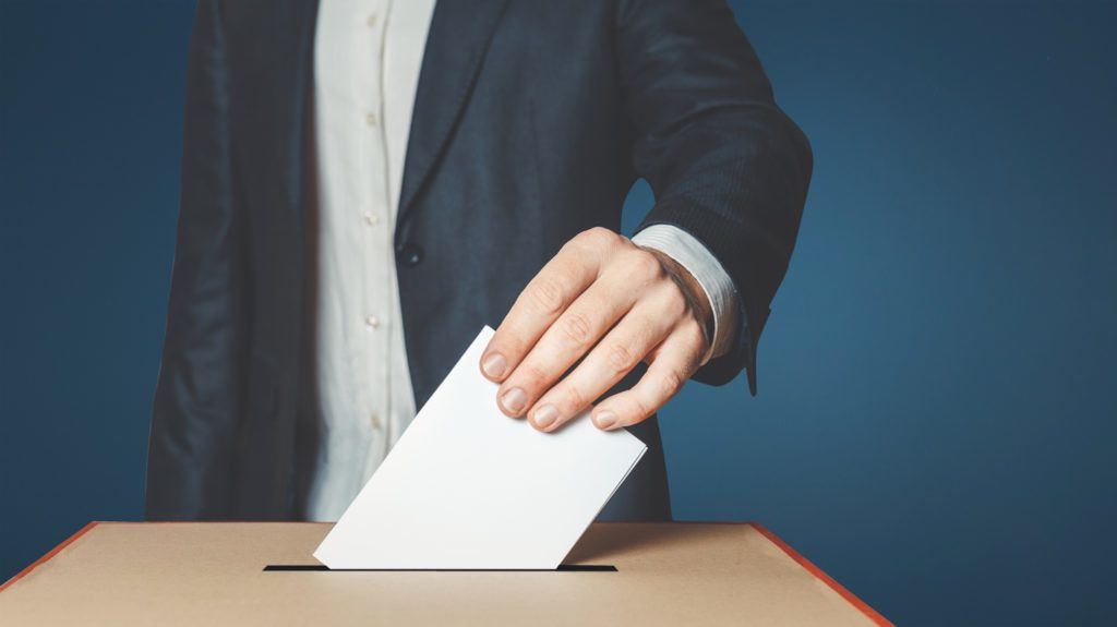 Unrecognizable male voter holds in his hand a ballot above the ballot box