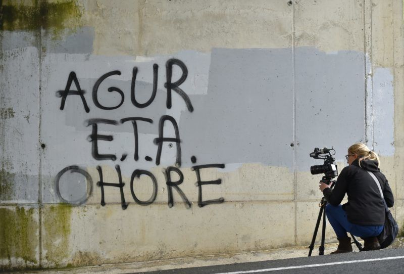 """A woman takes images of a graffiti reading in Basque """"ETA, Farewell and may you go with honor"""" in the Spanish Basque village of Agurain on May 3, 2018.  Spanish Prime Minister Mariano Rajoy said today there would be """"no impunity"""" for ETA's crimes even though the Basque separatist group is expected to formally announce its dissolution with a filmed statement, marking the definitive end to western Europe's last armed insurgency after more than four decades of violence. / AFP PHOTO / ANDER GILLENEA / TO GO WITH AFP STORY 'Farewell ETA, but Basque nationalism still strong' by Marianne BARRIAUX"""
