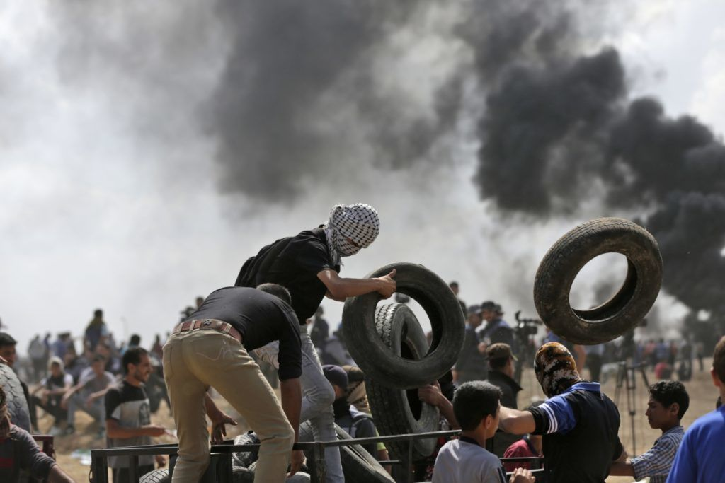 Palestinians carry tyres to be burnt during clashes with Israeli forces near the border between the Gaza strip and Israel east of Gaza City on May 14, 2018, during a demonstration on the day of the US embassy move to Jerusalem. The US moves its embassy in Israel to Jerusalem later Monday after months of global outcry, Palestinian anger and exuberant praise from Israelis over President Donald Trump's decision tossing aside decades of precedent. There are concerns that the Gaza protests less than 100 kilometres (60 miles) away will turn deadly if Palestinians attempt to damage or cross the fence with Israeli snipers positioned on the other side. / AFP PHOTO / MAHMUD HAMS