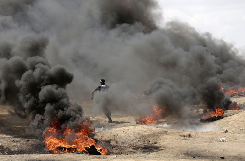 A Palestinian demonstrator runs as smoke billows from burning tyres during clashes with Israeli forces near the border between the Gaza strip and Israel east of Gaza City on May 14, 2018, during a demonstration on the day of the US embassy move to Jerusalem. / AFP PHOTO / MAHMUD HAMS