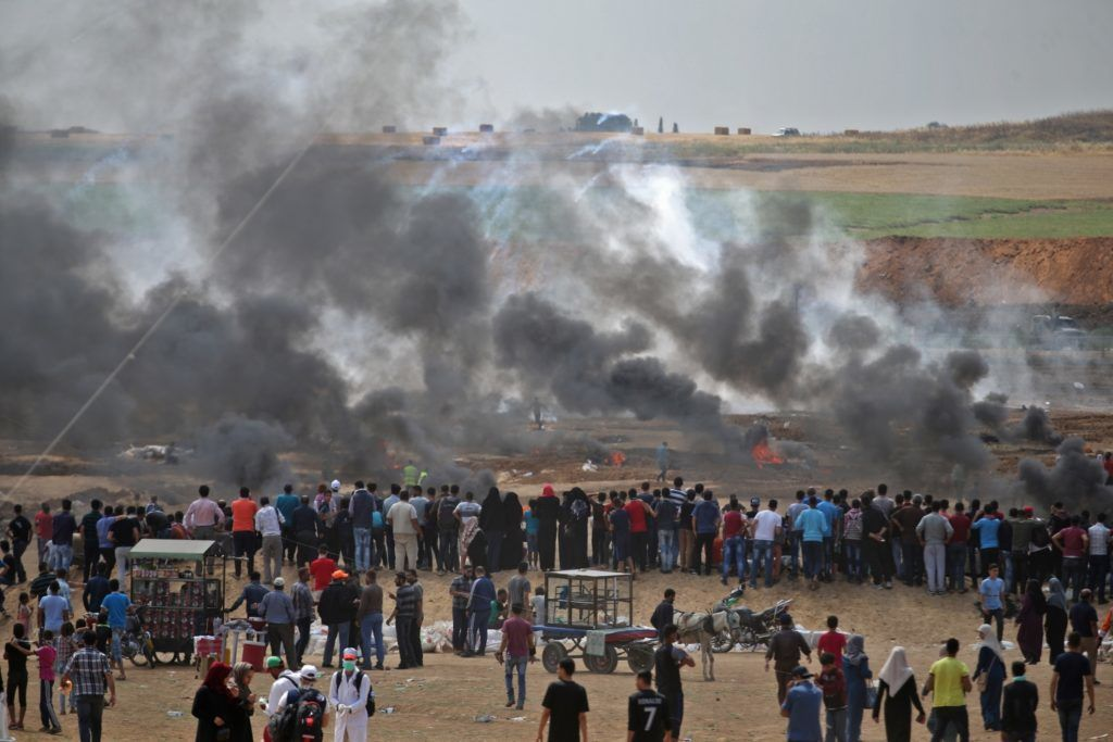 Palestinian protesters look at tear gas and smoke billowing from burning tyres, east of Gaza City on May 14, 2018, as Palestinians readied for protests over the inauguration of the US embassy following its controversial move to Jerusalem. / AFP PHOTO / Mohammed ABED