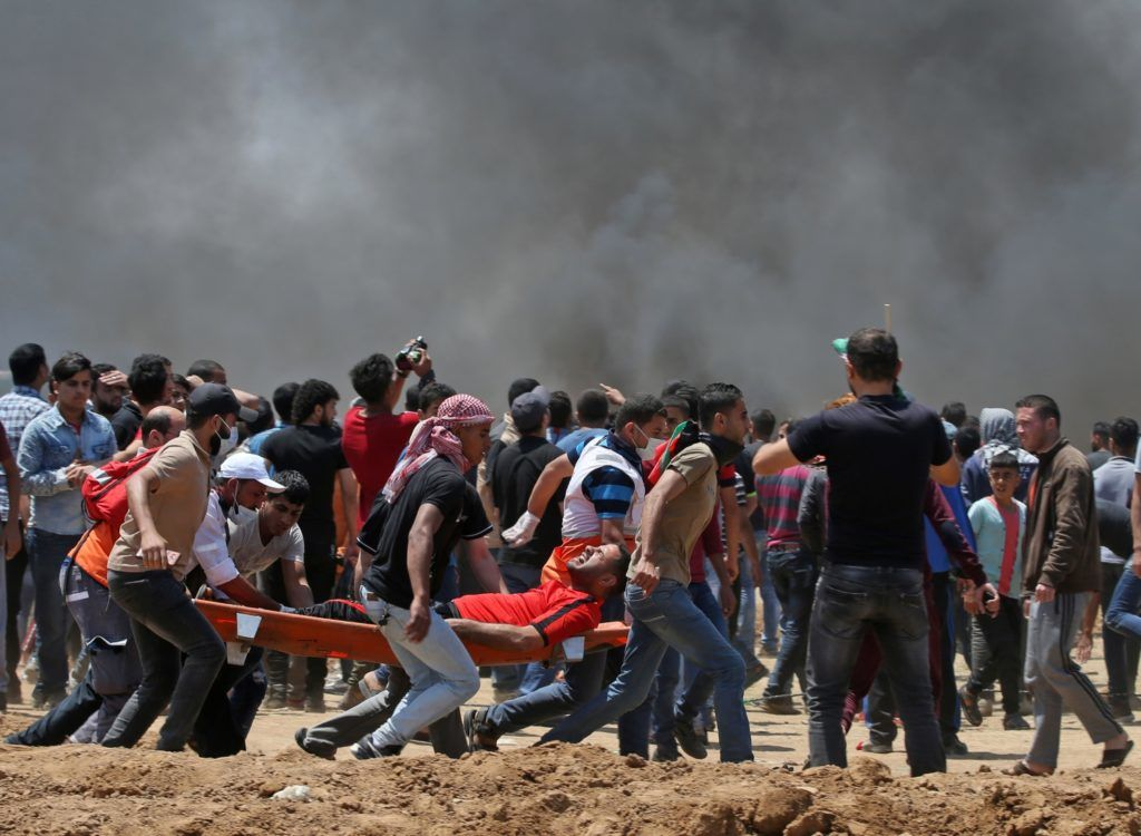 Palestinian men carry an innjured protester during clashes with Israeli forces near the border between Israel and the Gaza strip, east of Jabalia on May 14, 2018, as Palestinians readied for protests over the inauguration of the US embassy following its controversial move to Jerusalem. / AFP PHOTO / MOHAMMED ABED