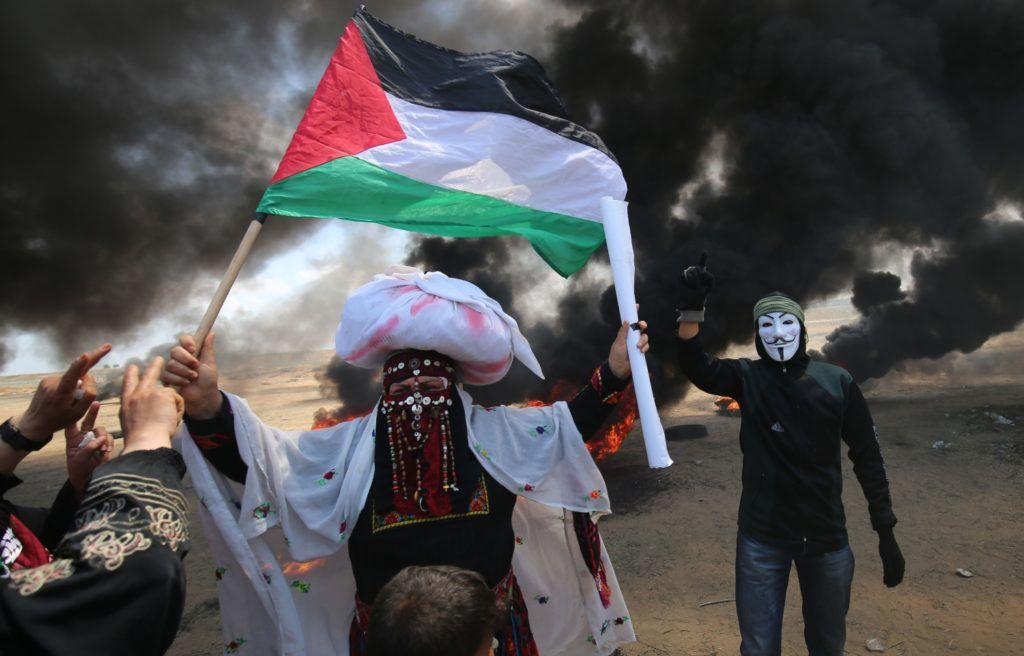 A Palestinian man holding his national flag walks in the smoke billowing from burning tyres next to a protester wearing an Anonymous mask during clashes with Israeli forces along the border with the Gaza strip east of Khan Yunis on May 14, 2018, as Palestinians protest over the inauguration of the US embassy following its controversial move to Jerusalem. / AFP PHOTO / SAID KHATIB