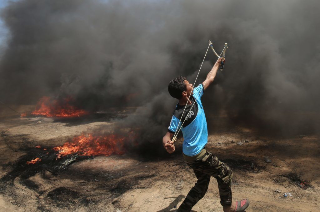 A Palestinian man uses a slingshot during clashes with Israeli forces along the border with the Gaza strip east of Khan Yunis on May 14, 2018, as Palestinians protest over the inauguration of the US embassy following its controversial move to Jerusalem. / AFP PHOTO / SAID KHATIB