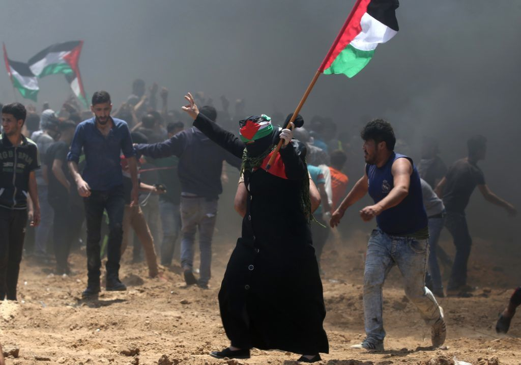 A Palestinian woman waves her national flag during clashes with Israeli forces near the border between Israel and the Gaza Strip, east of Jabalia on May 14, 2018, as Palestinians protest over the inauguration of the US embassy following its controversial move to Jerusalem. / AFP PHOTO / MOHAMMED ABED
