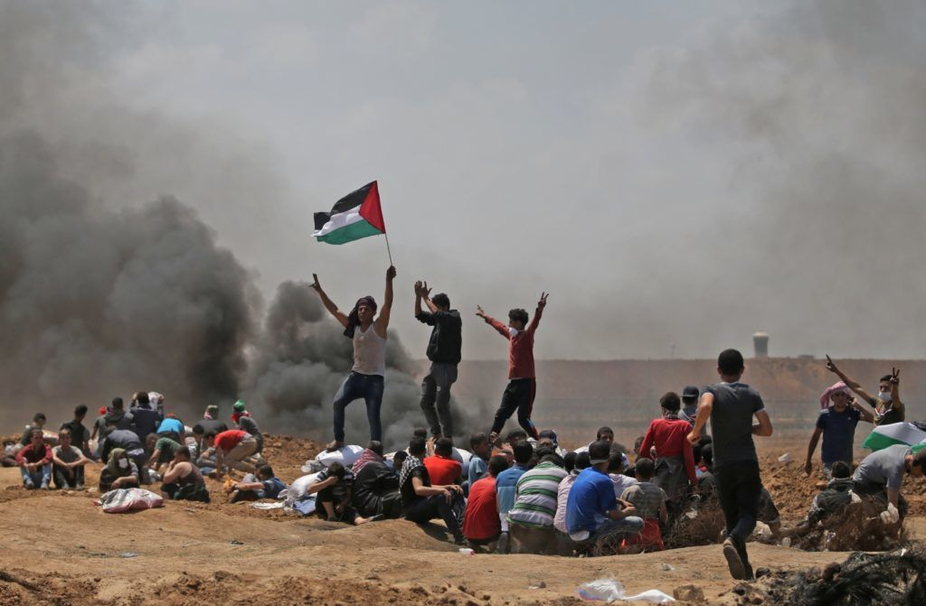 Palestinians wave their national flag as they demonstrate near the border between Israel and the Gaza Strip, east of Jabalia, against the inauguration of the US embassy following its controversial move to Jerusalem on May 14, 2018. / AFP PHOTO / MOHAMMED ABED