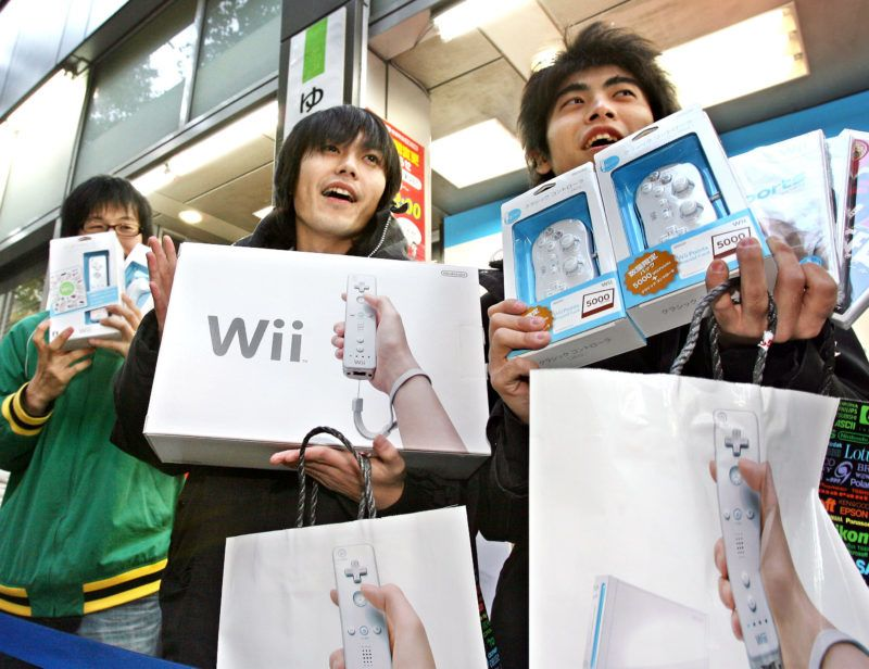 """Japanese customers display Nintendo's new video game console """"Wii"""" they purchased at a Tokyo electric shop, 02 December 2006. Thousands video game fans queued in early morning to buy the new video game console priced 25,000 yen (215 USD).      AFP PHOTO / Yoshikazu TSUNO / AFP PHOTO"""