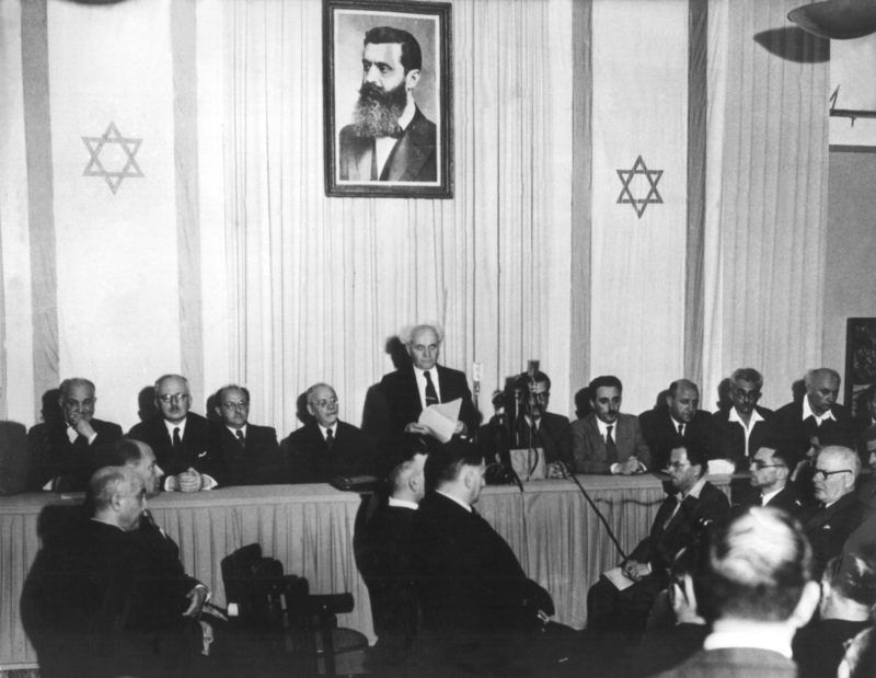 The designated Prime Minister David Ben Gurion (m) reads Israel's independance declaration in Tel Aviv's museum in Israel. Picture taken on the 13th of May in 1948. The wall behind him is adorned with a picture of Theodor Herzl, the visionary of Zionism.