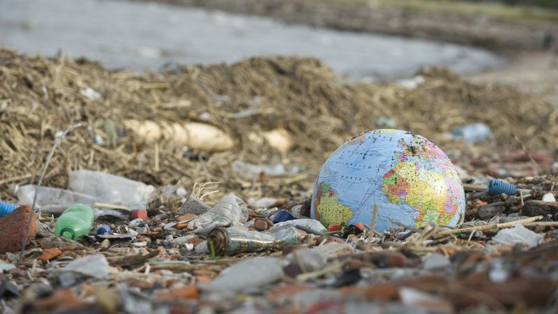 Globe partially buried in rubble and garbage littering beach