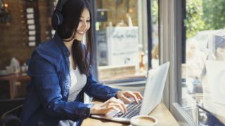 Young woman with headphones using laptop at sunny cafe window.