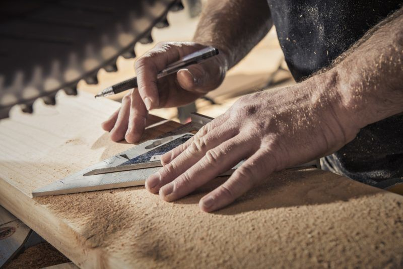 Close up of male carpenter with set square in workshop