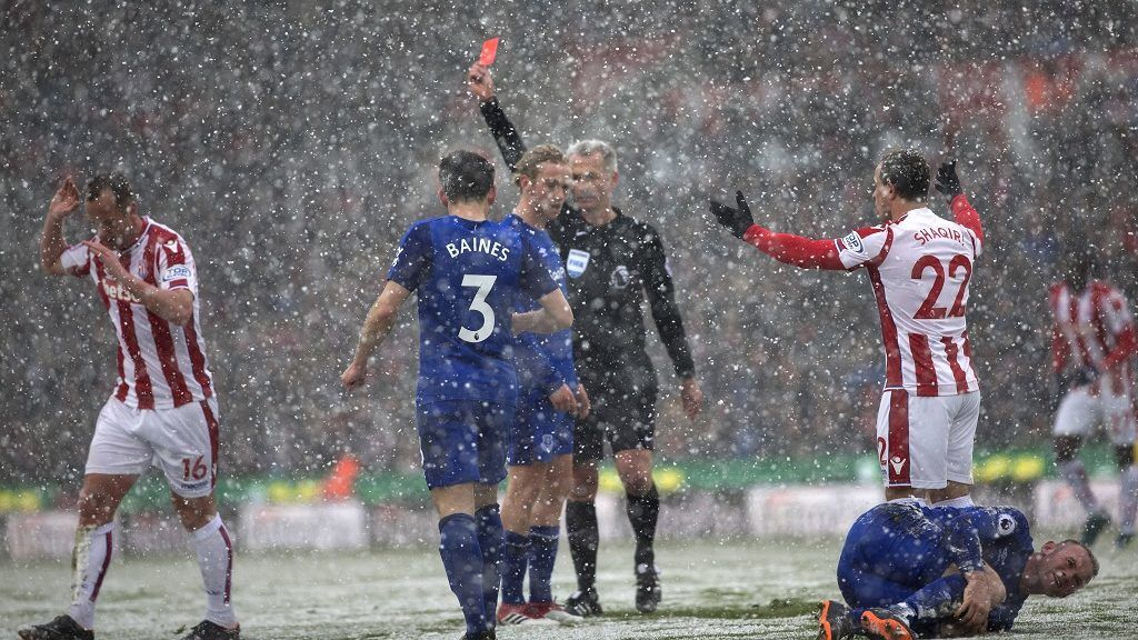 Referee Martin Atkinson (C) awards Stoke City's Scottish midfielder Charlie Adam (L) a red card as Everton's English striker Wayne Rooney (R) clutches his leg during the English Premier League football match between Stoke City and Everton at the Bet365 Stadium in Stoke-on-Trent, central England on March 17, 2018. / AFP PHOTO / Roland Harrison / RESTRICTED TO EDITORIAL USE. No use with unauthorized audio, video, data, fixture lists, club/league logos or 'live' services. Online in-match use limited to 75 images, no video emulation. No use in betting, games or single club/league/player publications.  /