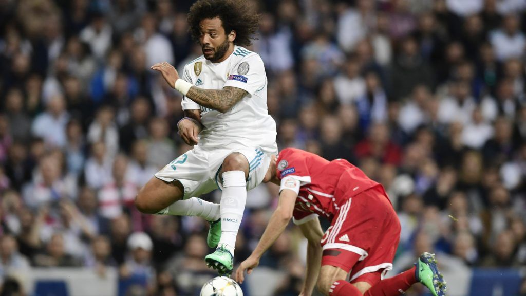 Real Madrid's Brazilian defender Marcelo (L) vies with Bayern Munich's German forward Thomas Mueller during the UEFA Champions League semi-final second leg football match between Real Madrid and Bayern Munich at the Santiago Bernabeu Stadium in Madrid on May 1, 2018. / AFP PHOTO / JAVIER SORIANO