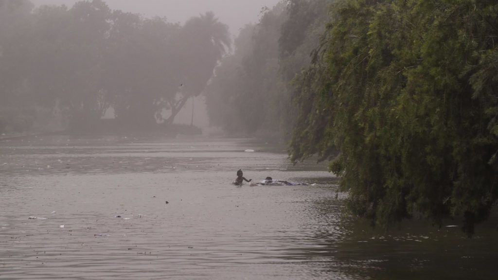 Indian children swim in a pond during a dust storm in New Delhi on May 2, 2018.  Dust storms tore across northern India killing at least 77 people and injuring 143 as trees and walls were flattened by powerful winds, officials said May 3. / AFP PHOTO / CHANDAN KHANNA