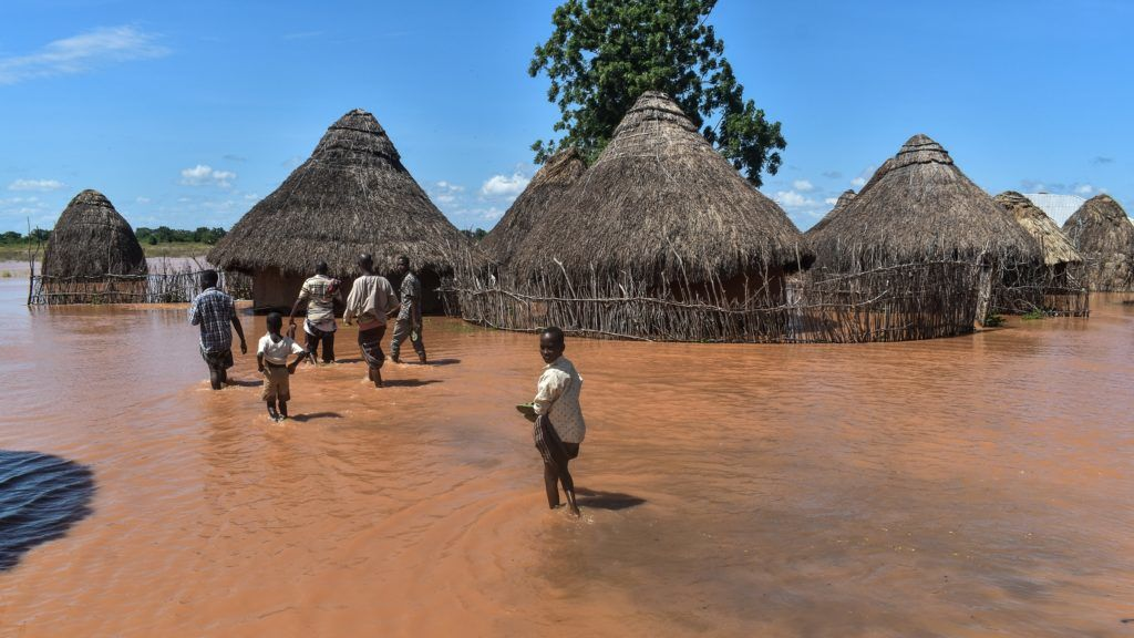 A picture taken on April 27, 2018 shows men and children walking in floodwaters after the Tana River overflowed at Onkolde Village, in coastal Tana Delta region of Kenya. About 64 000 people have displaced from the flooded area, according to Kenya Red Cross.  / AFP PHOTO / ANDREW KASUKU